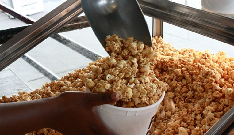 scooping kettle corn into plastic tub