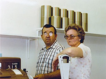 Everett Fisher working the counter register with woman