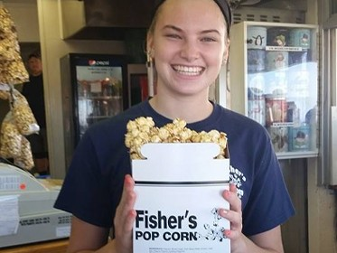 smiling young female clerk holding box of popcorn next to counter