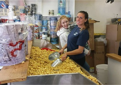 2 smiling young female employees in kitchen holding scoops dug into large pile of popcorn